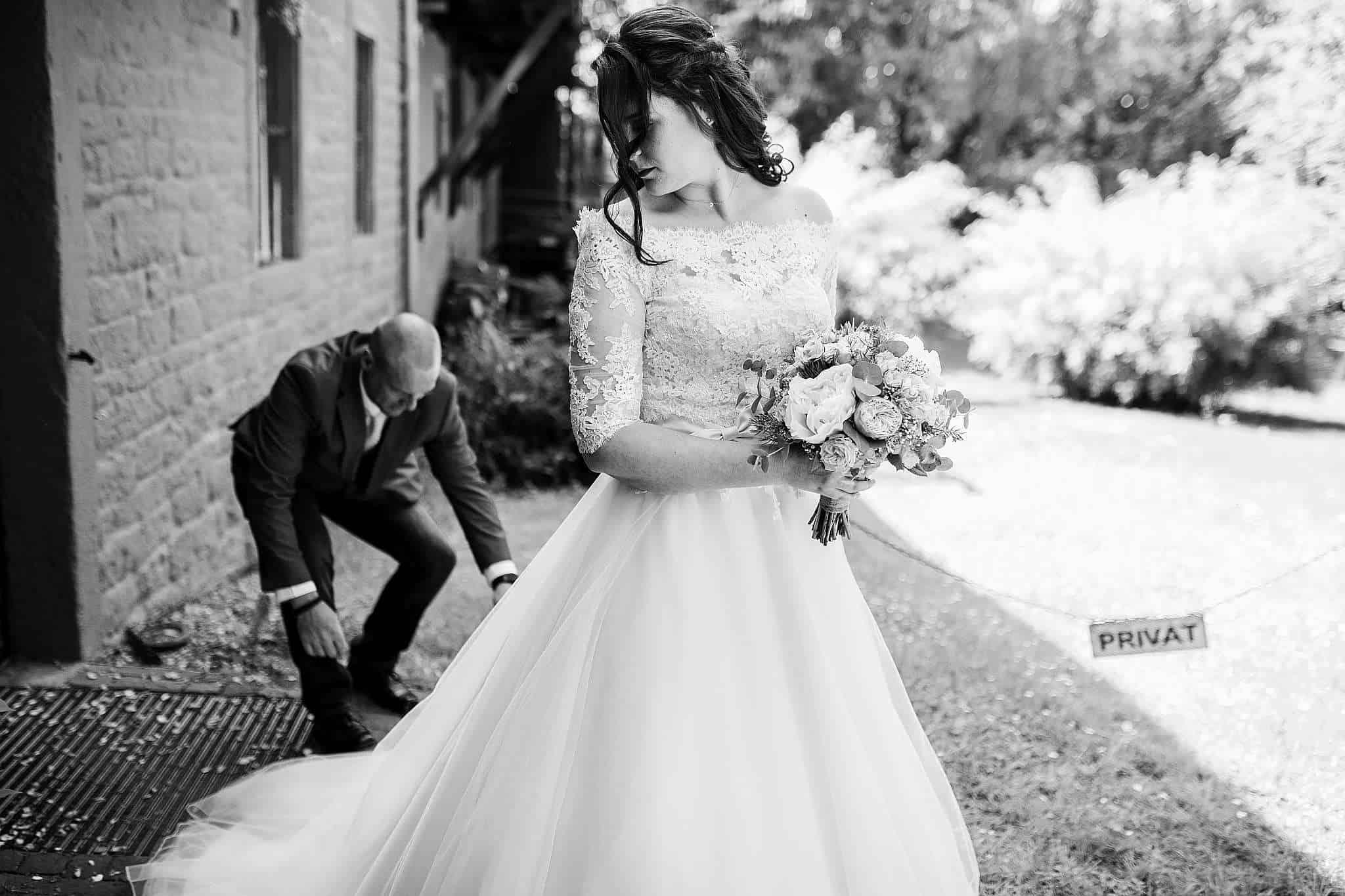 Der Bruder der Braut richtet das Kleid vor dem Einzug
