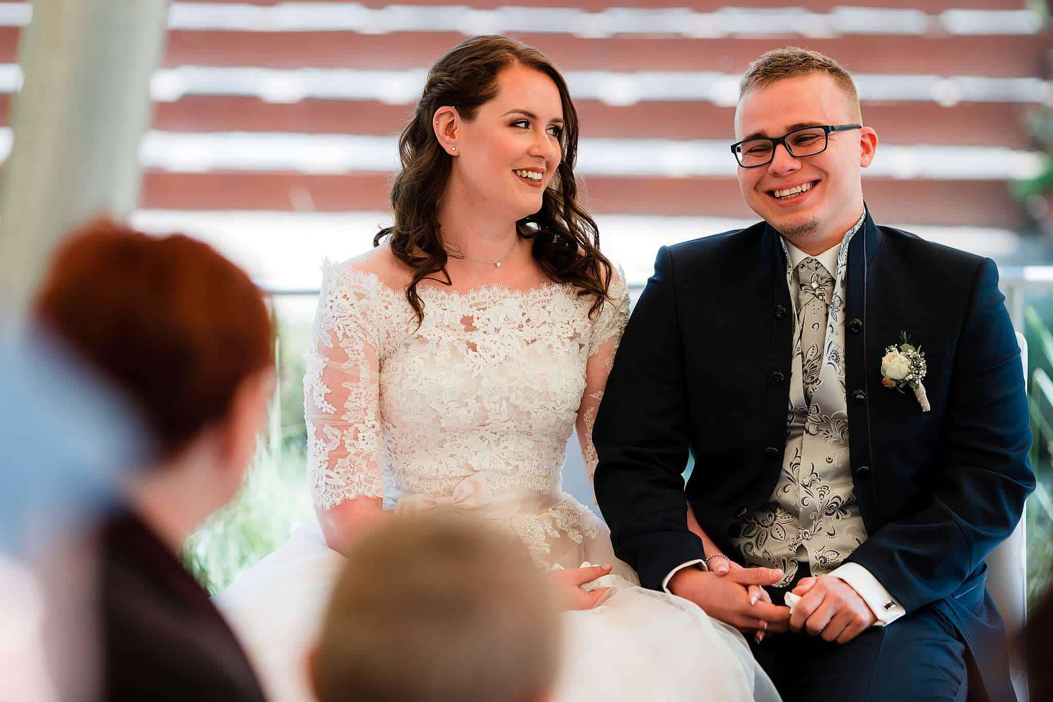 Das Brautpaar lacht während der Trauung