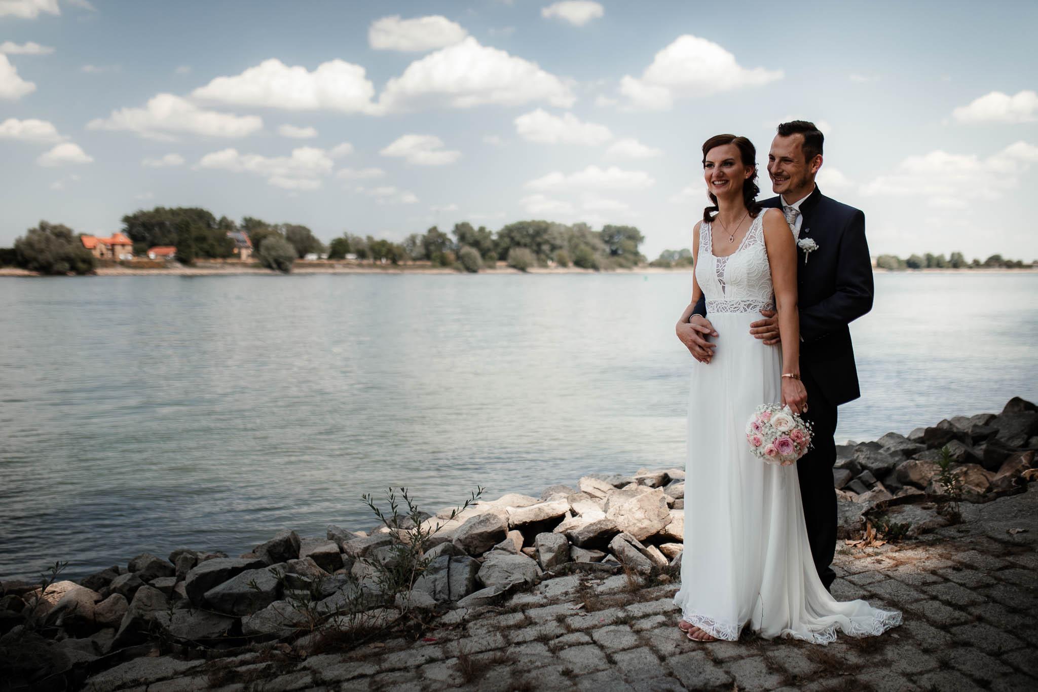 Hochzeitsfotos Oppenheim: Das Brautpaar steht am Rhein und albert herum