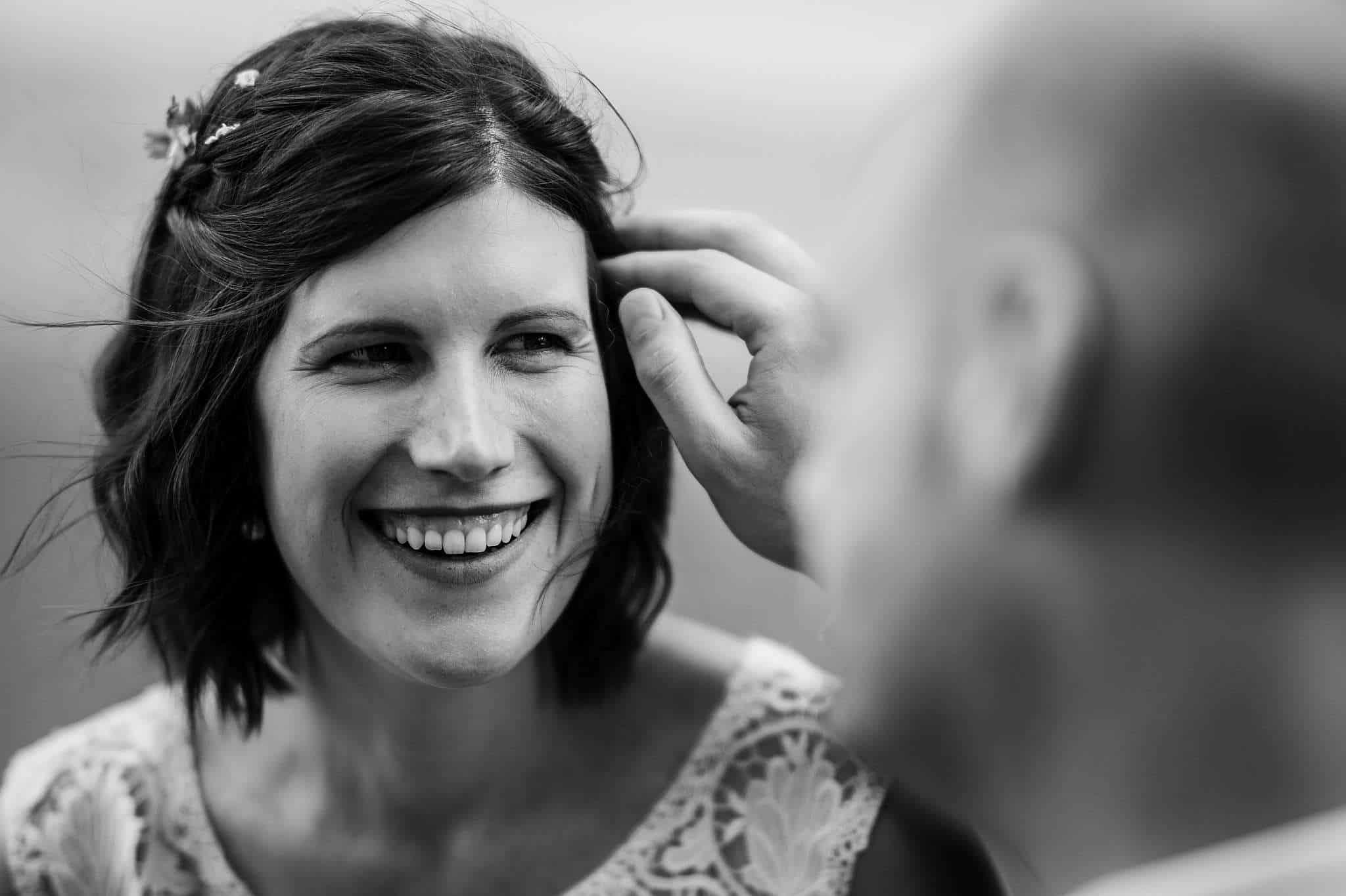 Hannes streicht Ina beim Brautpaarshooting in Guntersblumeine Haarsträhne aus dem Gesicht