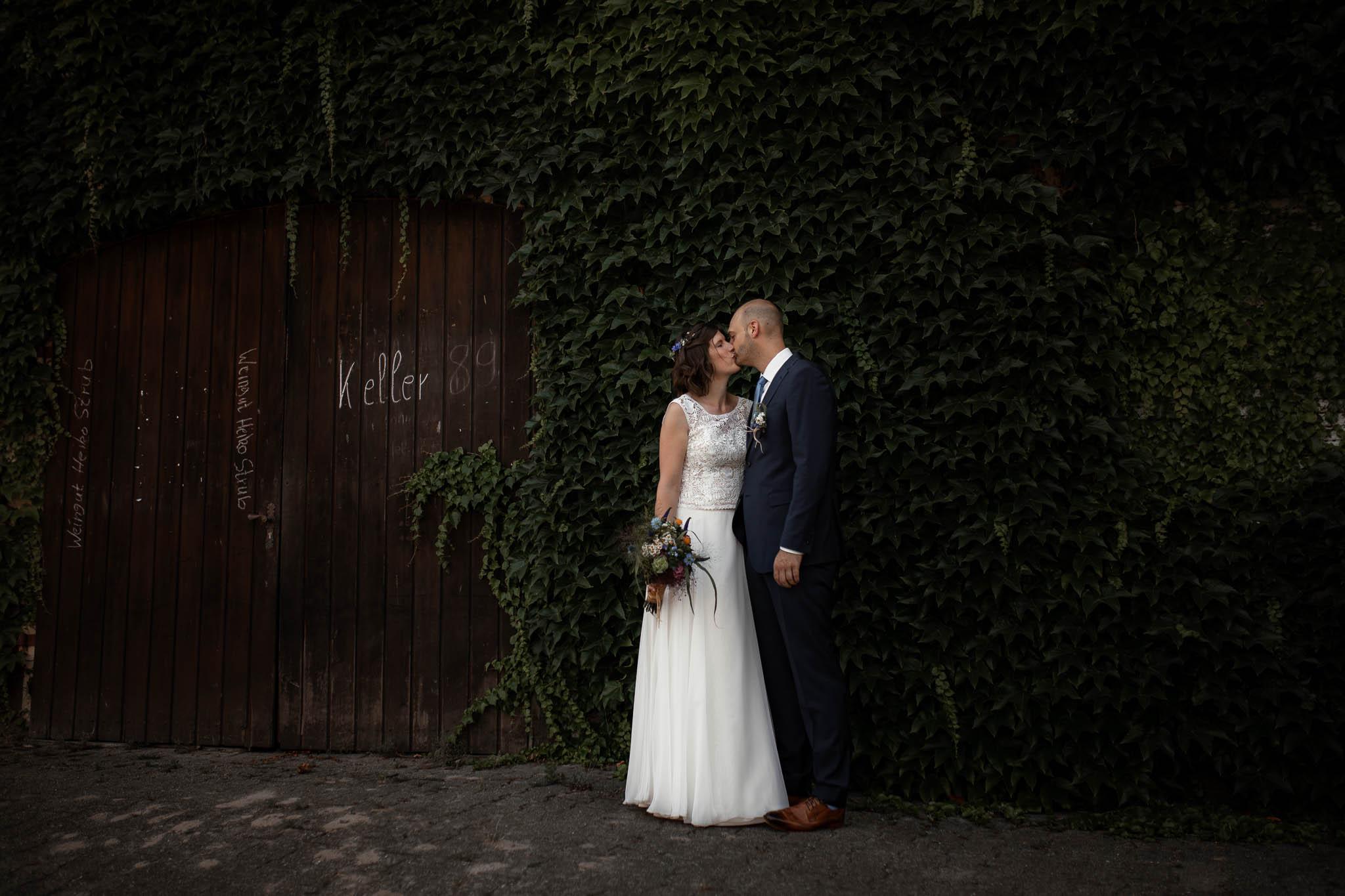 Hochzeitsfotograf Alzey:Ina und Johannes kuscheln beim Shooting vor einer mit Efeu bewachsenen Mauer in Guntersblum