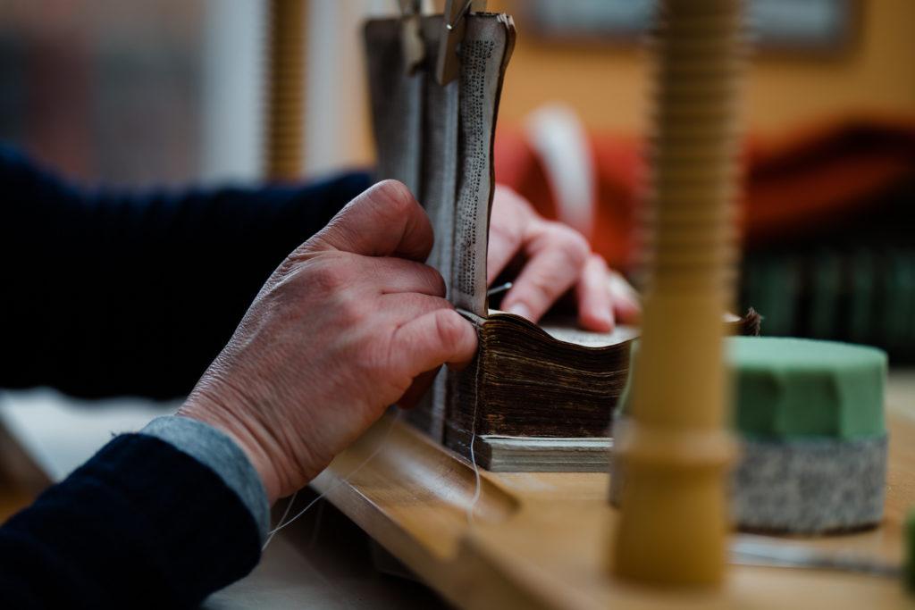 vorsichtig wird mit Nadel und Faden jede Seite im Buch befestigt