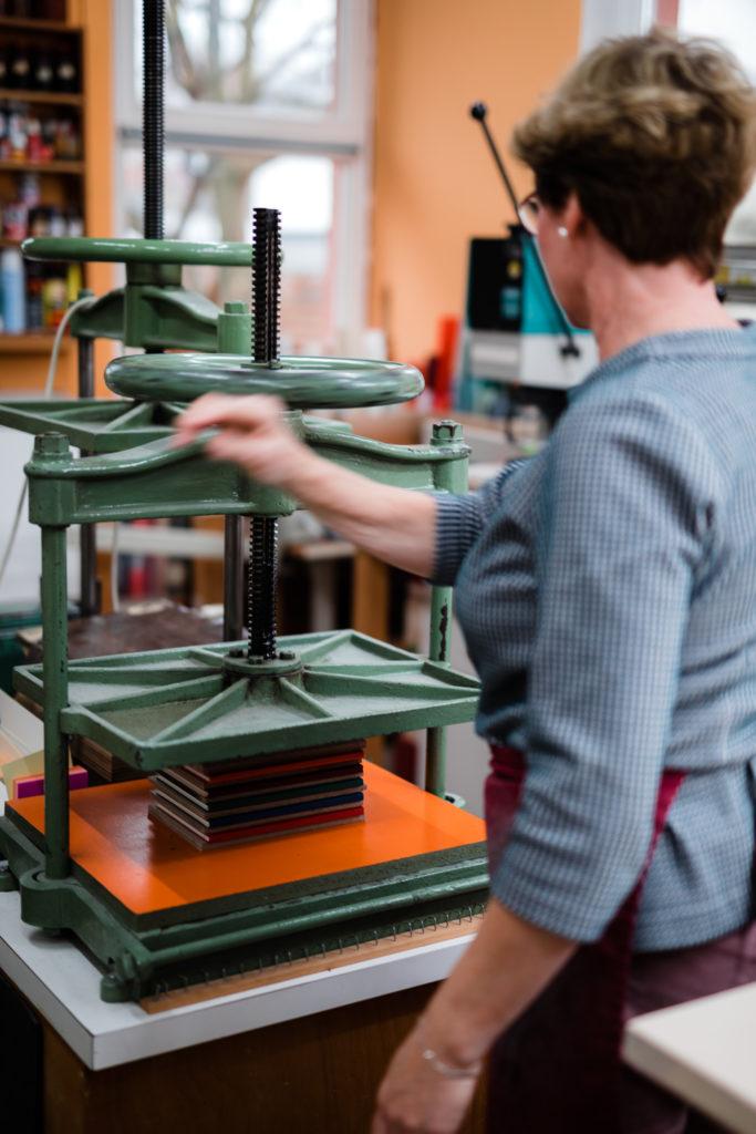 Bücher werden zum Trocknen des Klebers in die Buchpresse gespannt