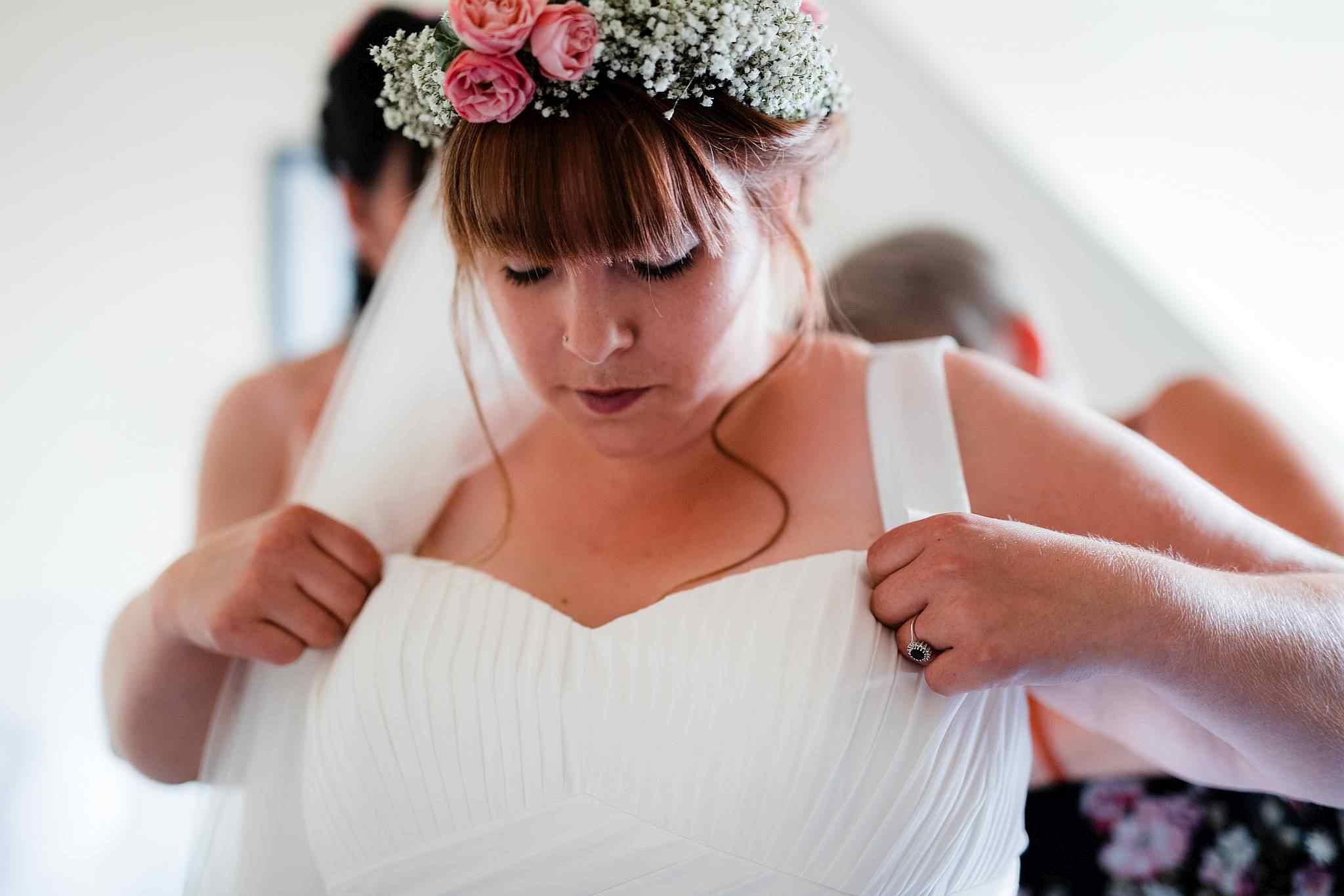 Die Braut schlüpft ins Hochzeitskleid