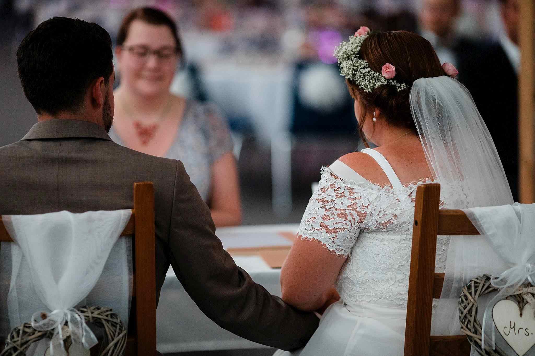 Das Brautpaar hält während der freien Trauung Händchen