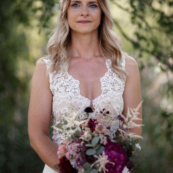 Auf diesem Bild sieht man eine Braut mit einem Brautstrauß.
