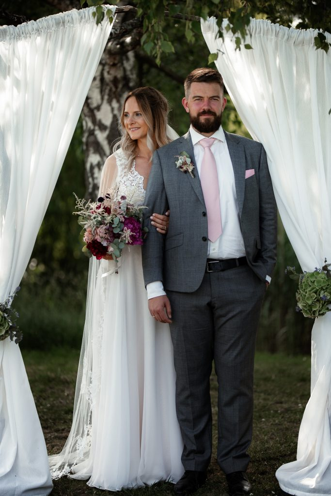 Das Bild zeigt das Brautpaar unter einem Traubogen.
