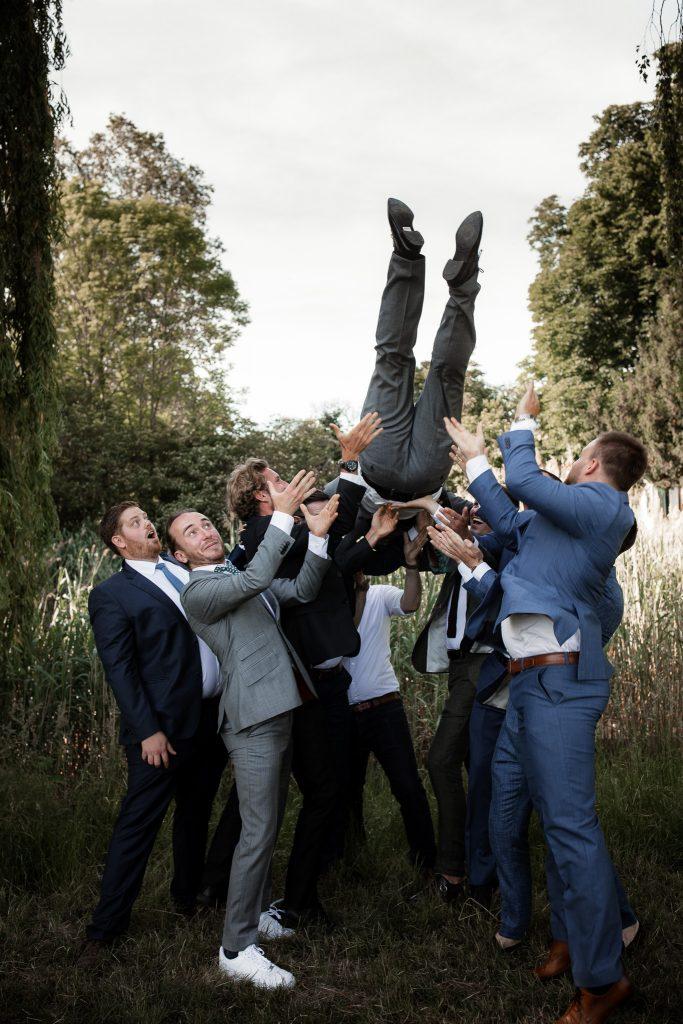 Die Kumpel des Bräutigams werfen ihn hoch.