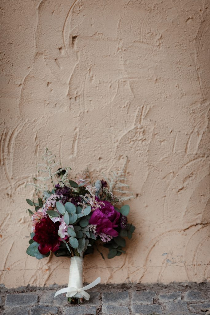 Brautstrauß lehnt an einer Wand.
