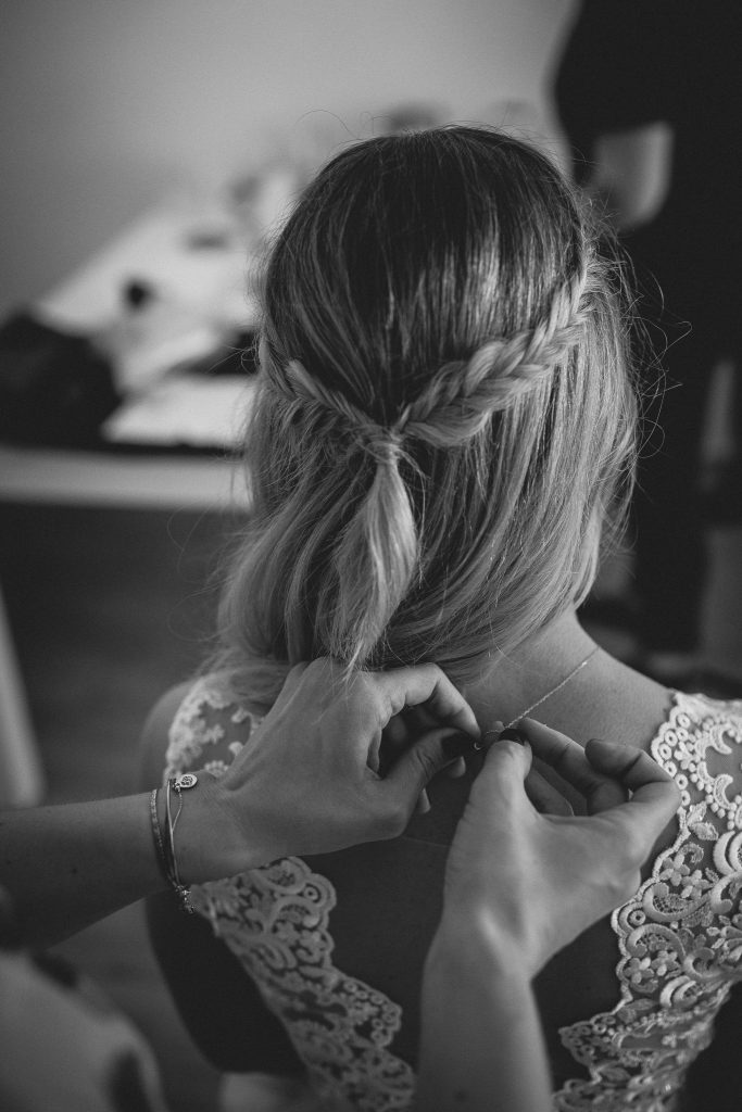 Die Trauzeugin legt der Braut ihren Schmuck an.