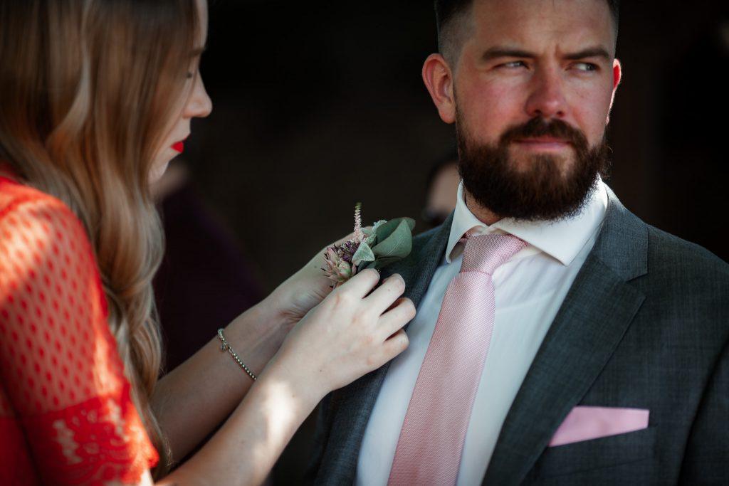 Der Bräutigam bekommt seinen Blumenanstecker von einer Freundin angesteckt.