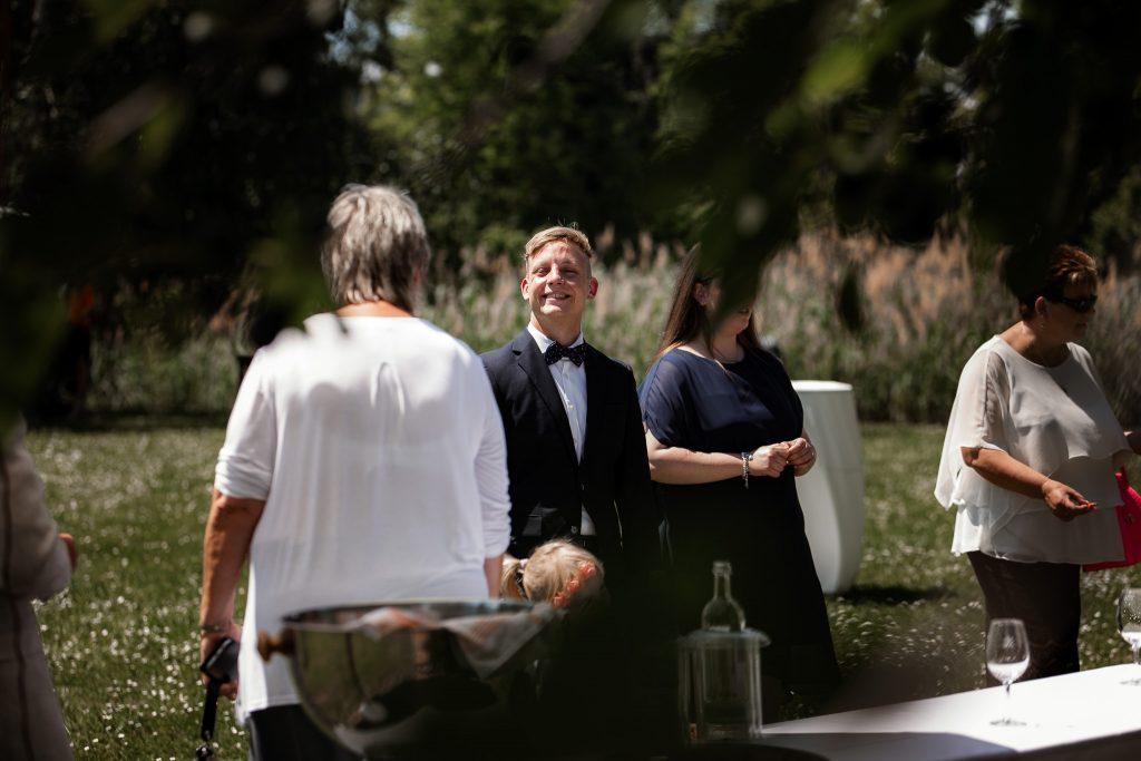 Hochzeitsgäste sitzen auf einer Wiese