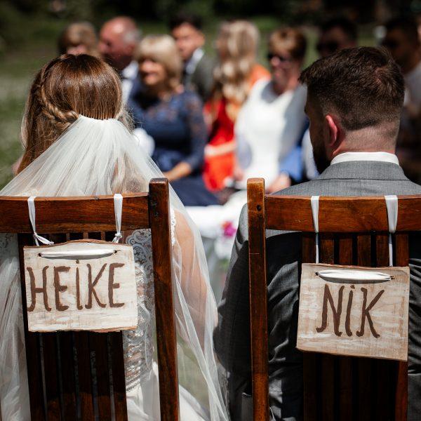 Das Brautpaar sitzt bei der freien Trauung mit Blick zu den Gästen.