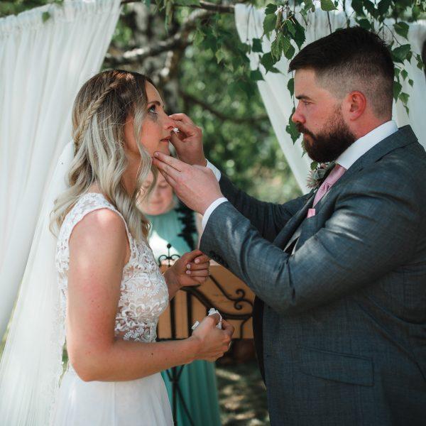 Der Bräutigam trocknet die Tränen der Braut nach dem Eheversprechen.