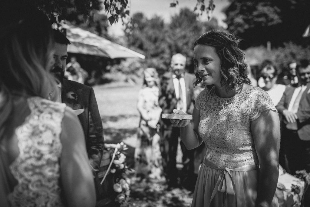 Die Schwester der Braut bringt die Eheringe nach vorne.
