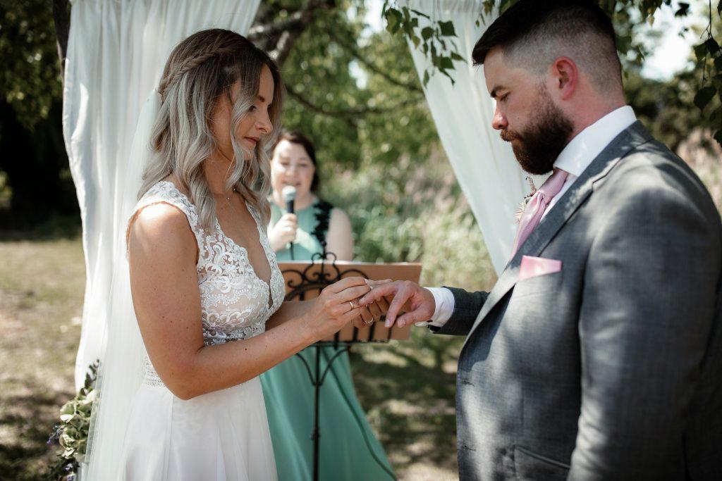 Das Brautpaar steckt sich die Eheringe an, moderiert von der freien Rednerin.