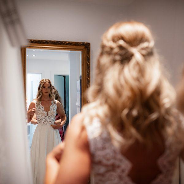 Die Braut schaut sich zum ersten Mal im Spiegel an.