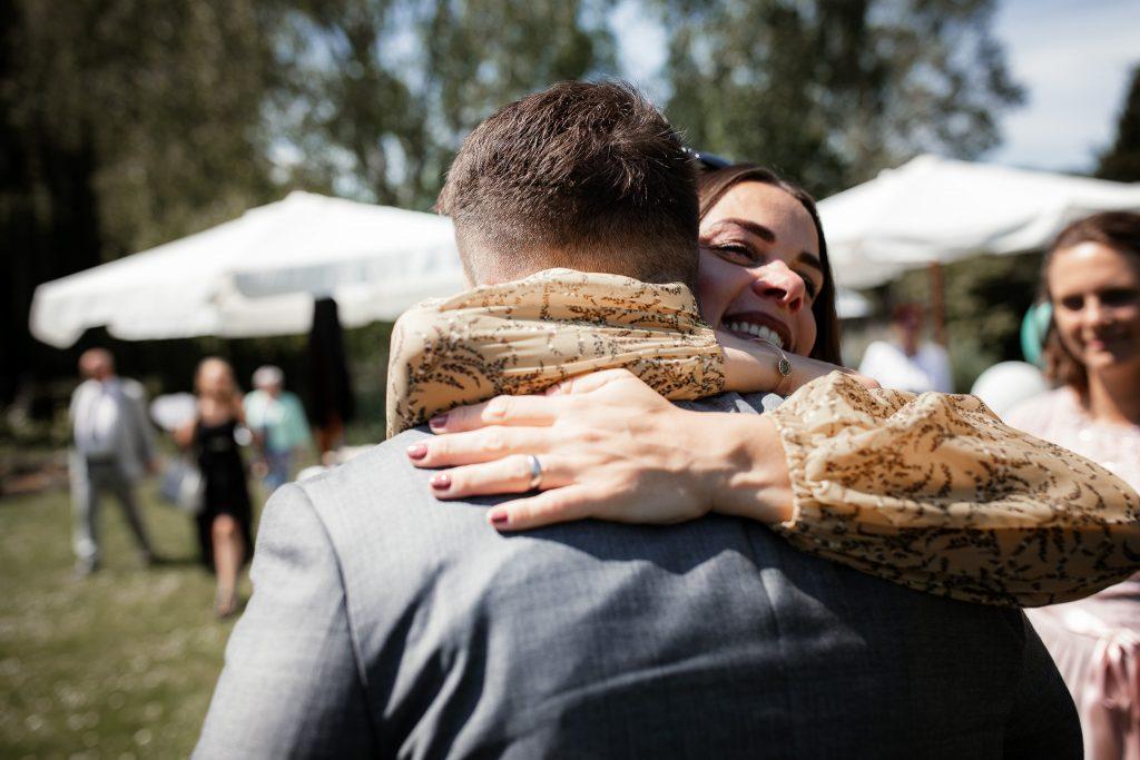 Freundin des Brautpaares gratuliert dem Bräutigam.