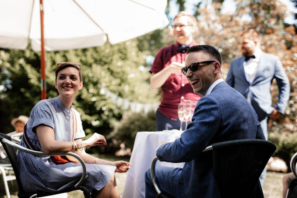 Hochzeitsgäste sitzen zusammen und unterhalten sich.
