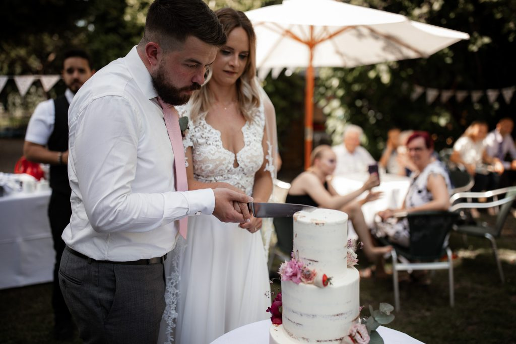 Das Brautpaar schneidet die Hochzeitstorte an.