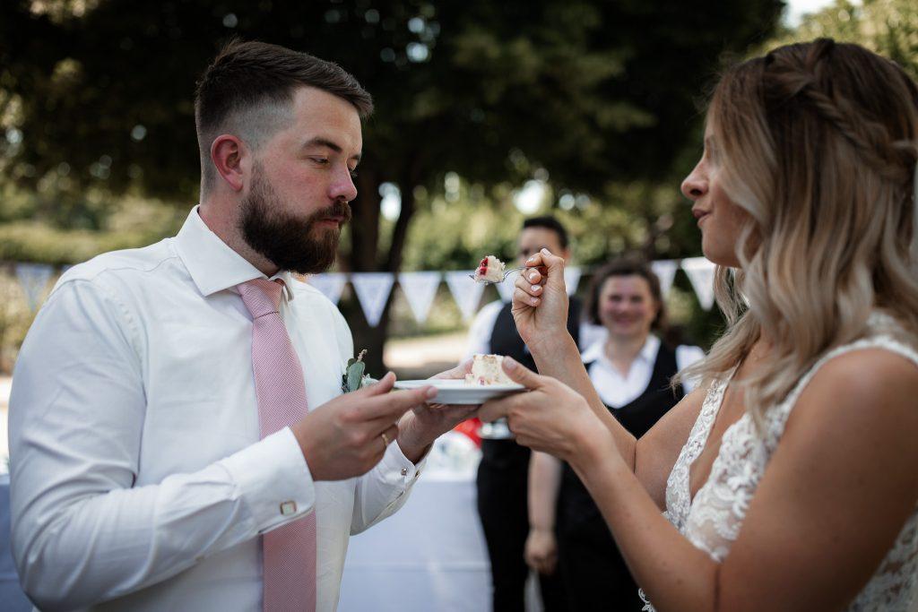 Das Brautpaar füttert sich mit Hochzeitstorte.