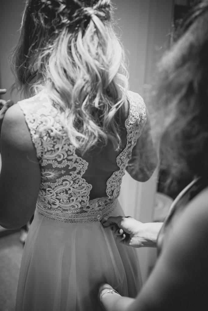 Die Trauzeugin schließt das Brautkleid der Braut.