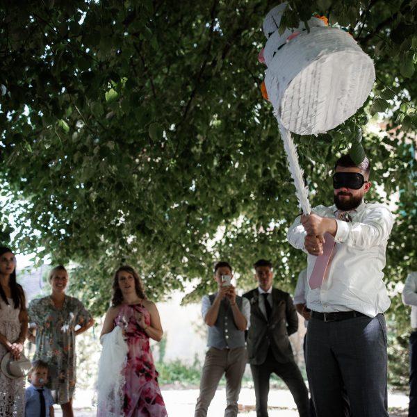 Der Brautpaar zerschlägt mit verbundenen Augen eine Pinata.