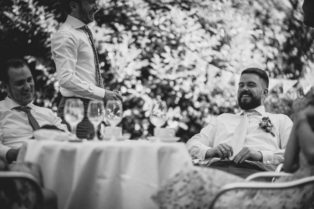 Der Bräutigam sitzt bei seinen Gästen.