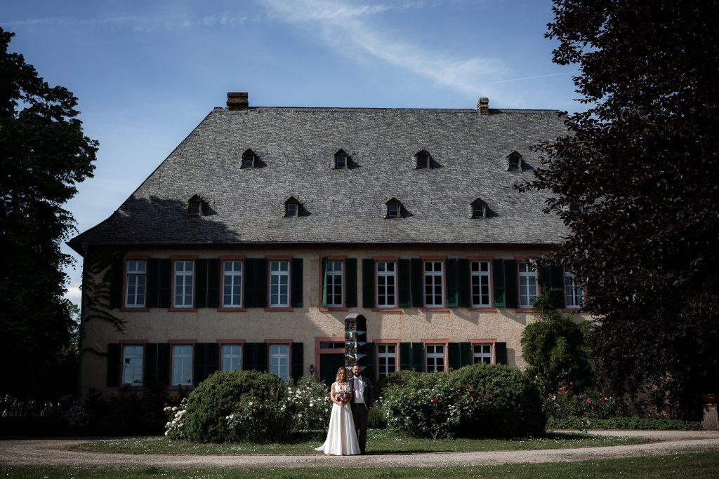 Hochzeitsfotograf Knyphausen Eltville: Brautpaar steht vor dem Herrenhaus im Weingut Knyphausen