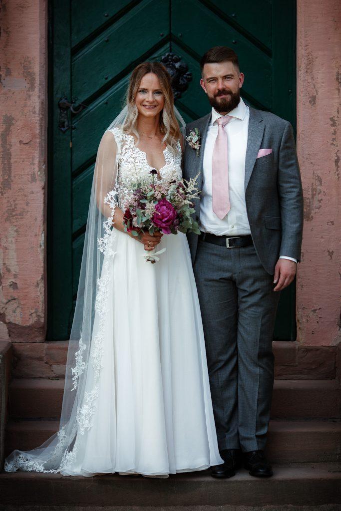 Das Brautpaar steht vor der Tür eines Herrenhauses und schaut in die Kamera.