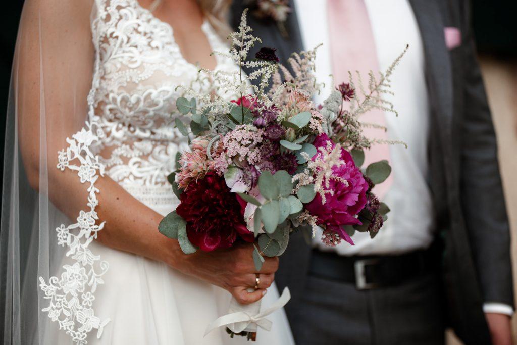 Dieses Bild zeigt einen Teilausschnitt der Braut mit dem Fokus auf dem Brautstrauß.