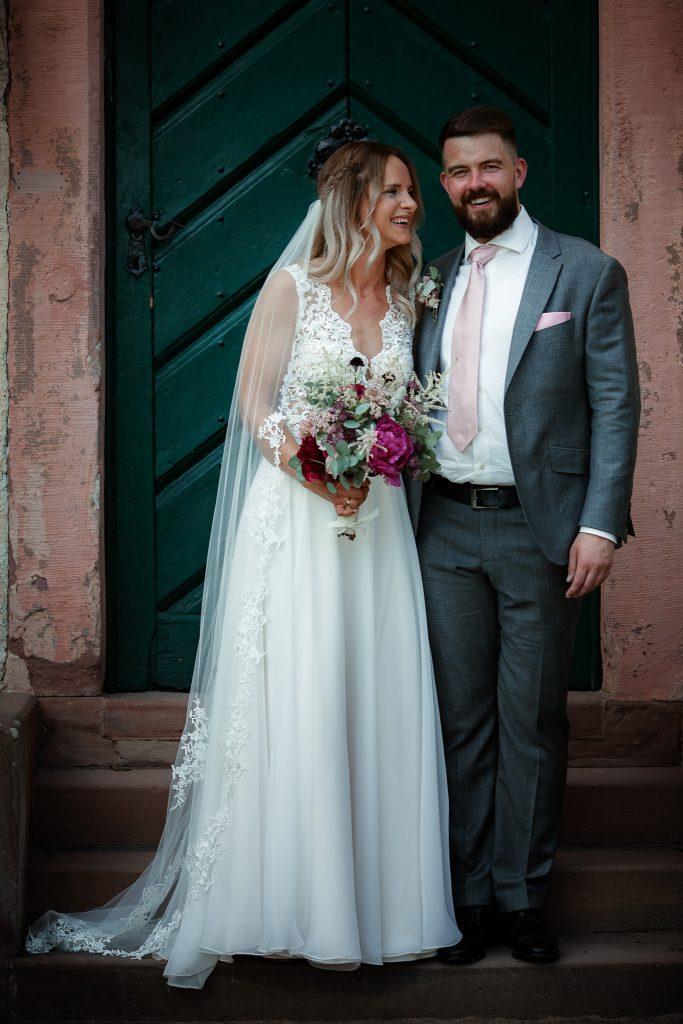 Das Brautpaar steht vor der Tür eines Herrenhauses.