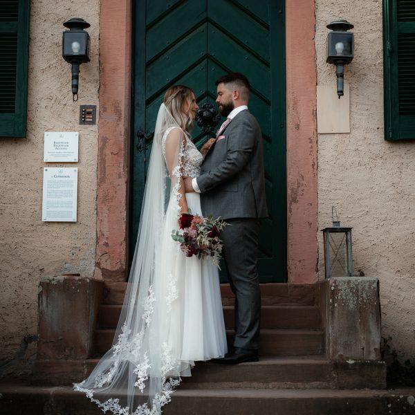 Das Brautpaar steht vor der Tür eines Herrenhauses und schaut sich an.
