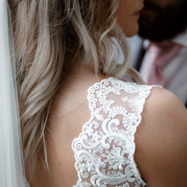 Teilausschnitt der Braut mit dem Fokus auf die Spitze am Brautkleid