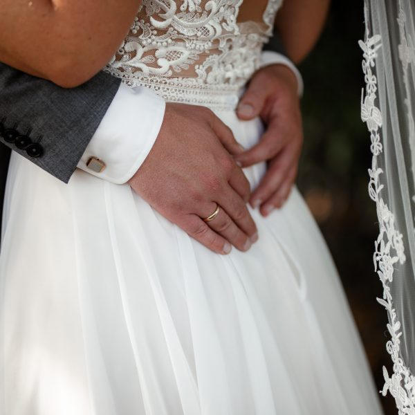Der Bräutigam legt seine Hände um die Hüfte der Braut.