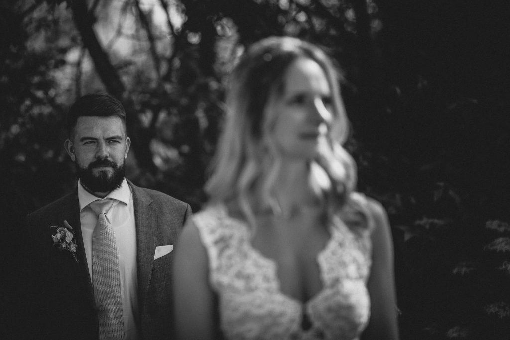 Das Bild zeigt den Bräutigam, die Braut ist unscharf im Vordergrund zu sehen.