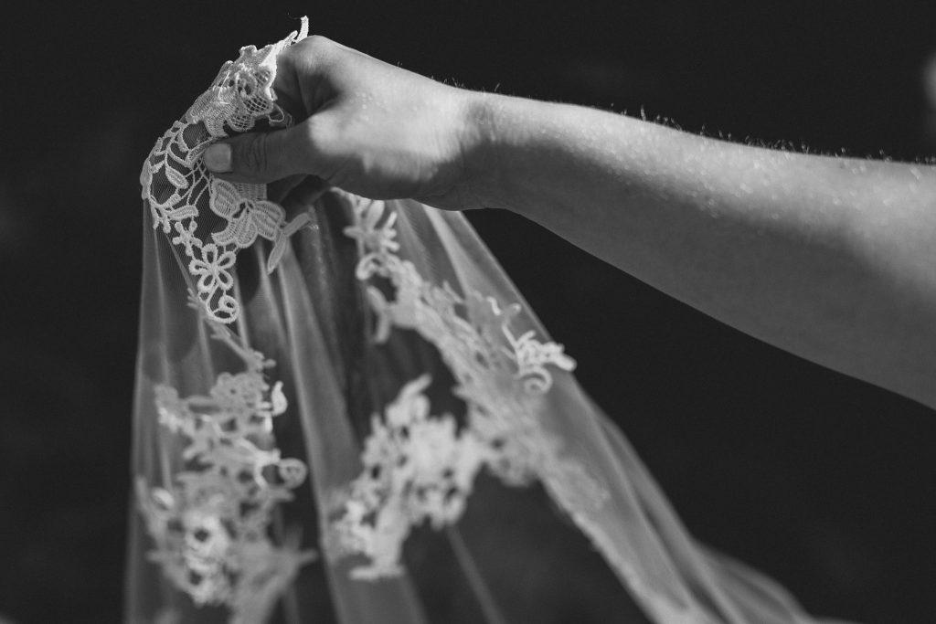 Die Braut trägt den Schleier in einer Hand.
