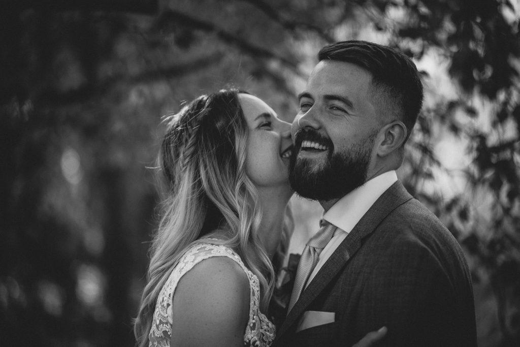 Das Bild zeigt eine Braut, die ihren Bräutigam auf die Wange küsst.