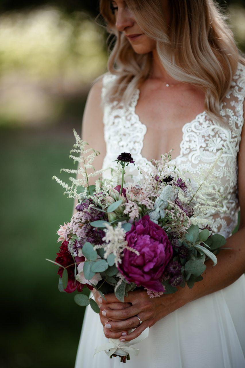 Auf dem Bild sieht man einen Brautstrauß in Beerentönen.